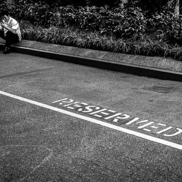 Ein Mann, der am Straßenrand sitzt.