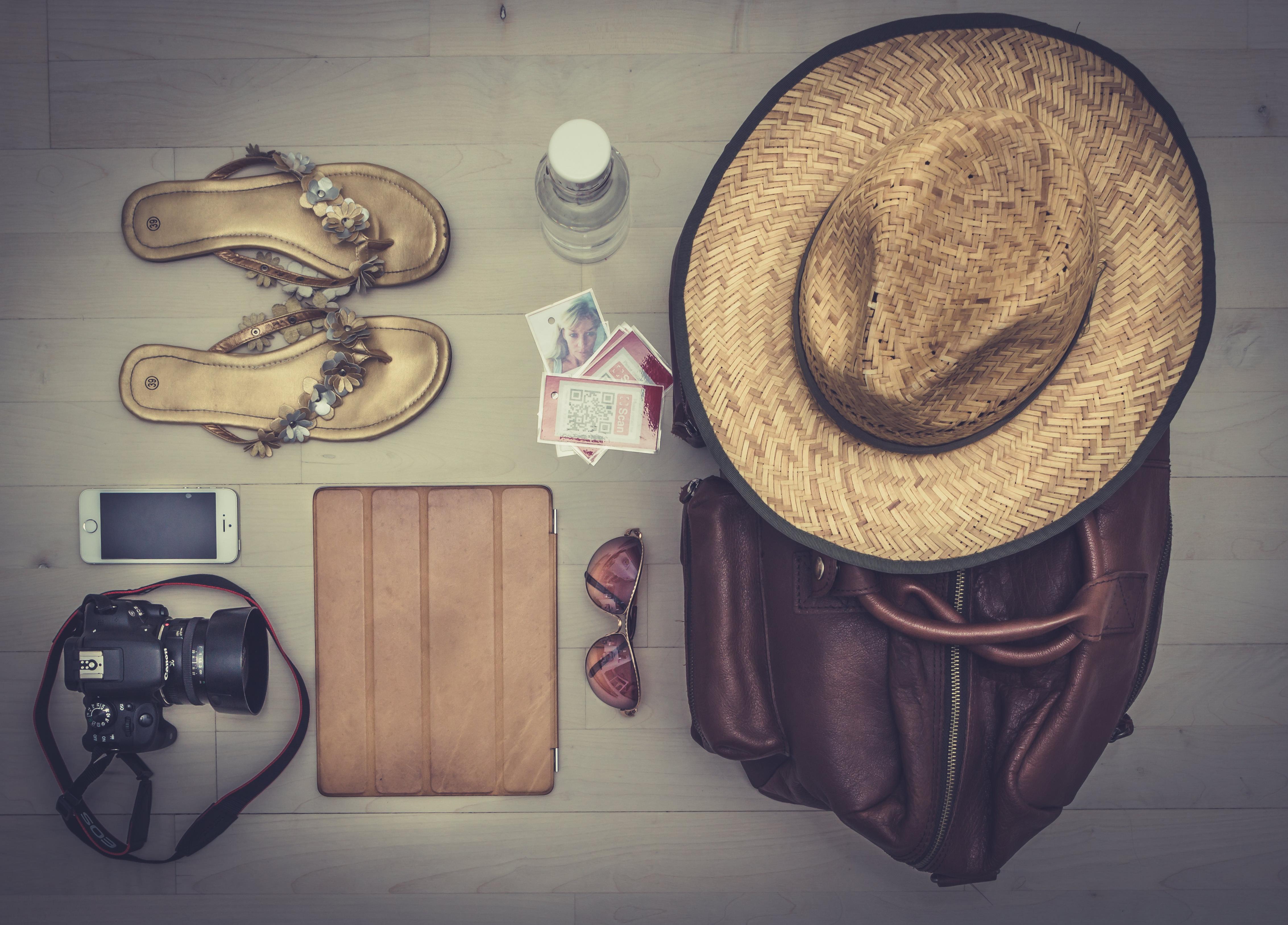 Die Sommerausrüstung einer Fotografin – Strohhut, Smartphone, Tablet und Spiegelreflexkamera.