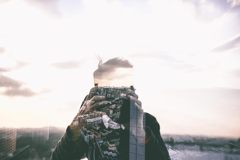 Doppelbelichtung: Junger Mann mit Kamera verschwimmt mit Aufnahmen einer Stadt aus erhöhter Perspektive.