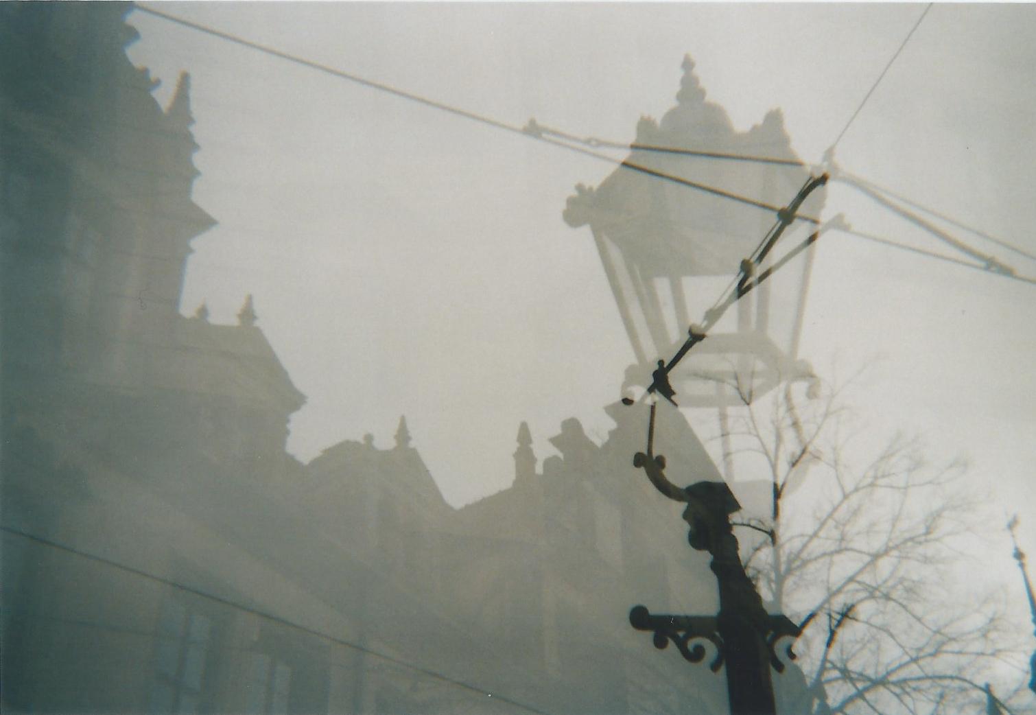 Doppelbelichtung von Häuserfront und einer alten Straßenlaterne
