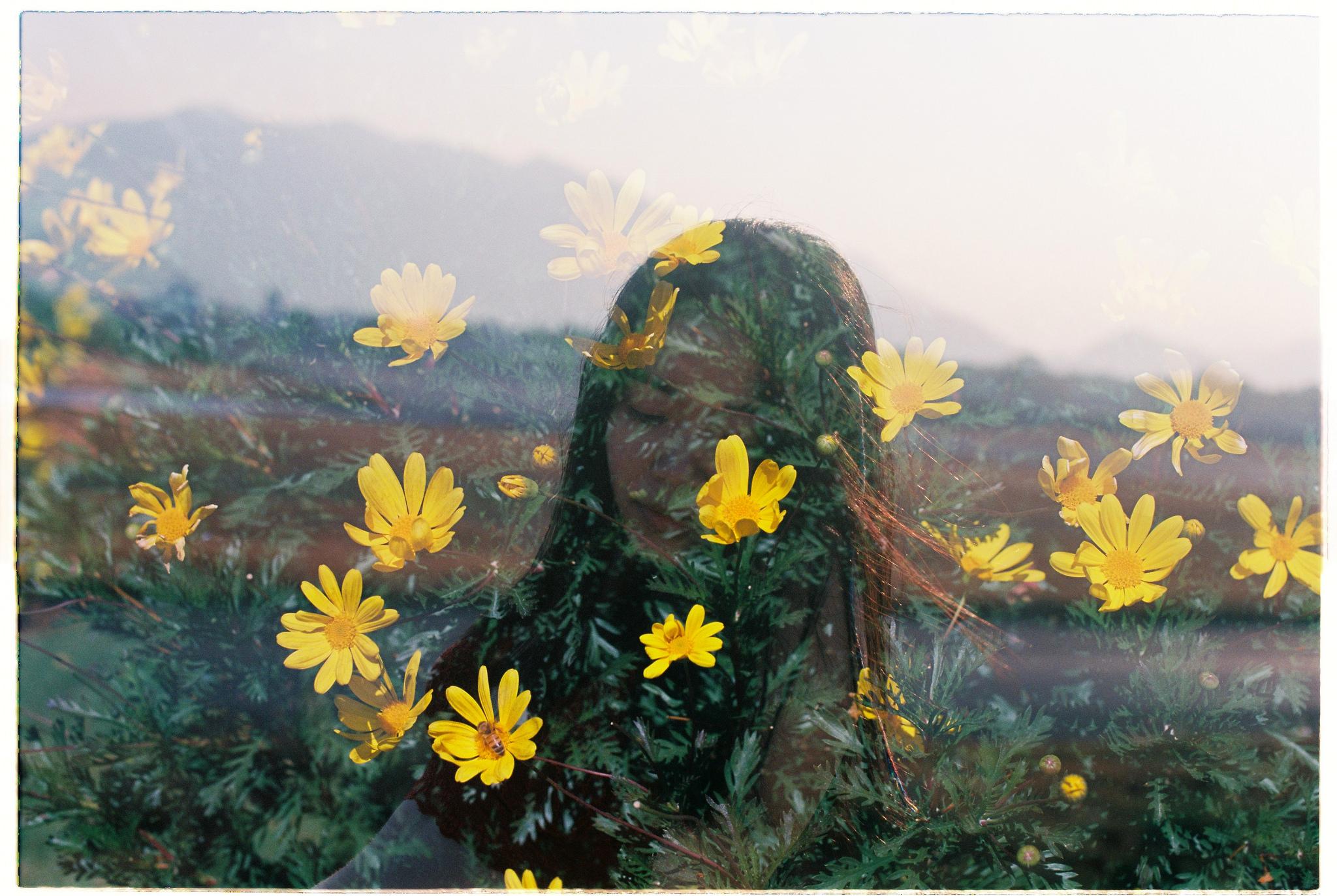 Doppelbelichtung – verträumte junge Frau und gelbe Blüten.