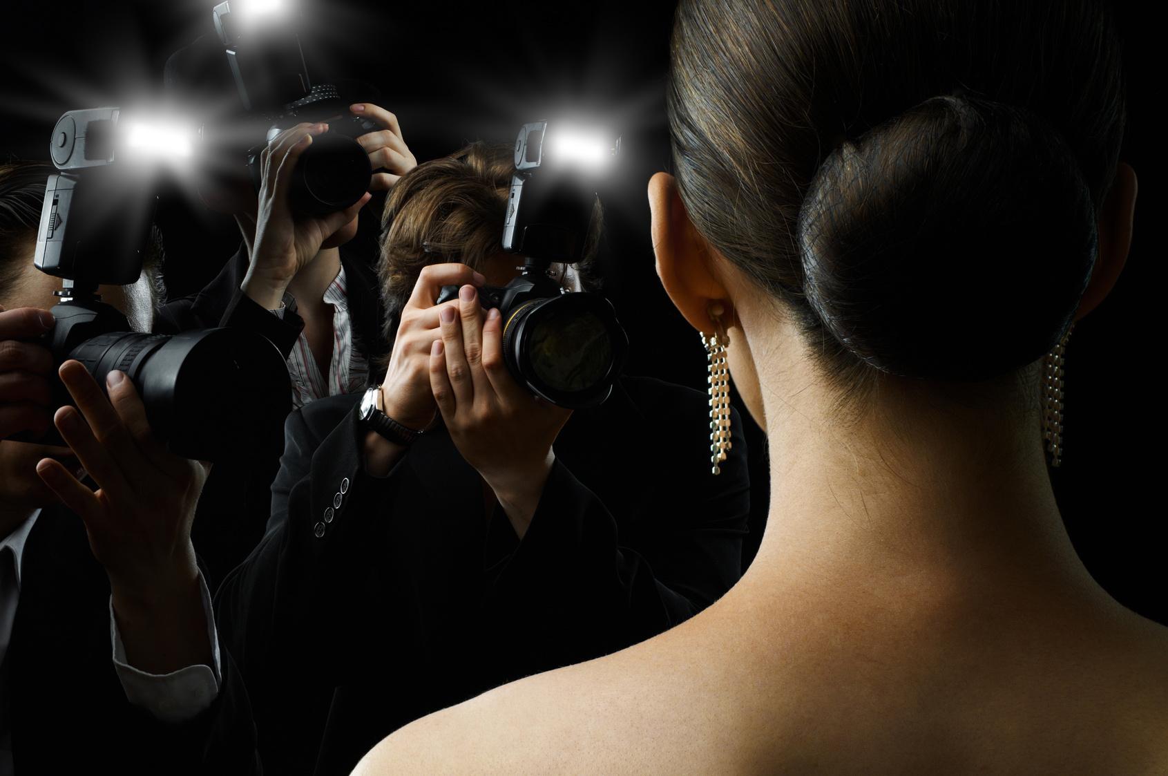 Blick über die Schulter einer Frau, die für Fotografen posiert