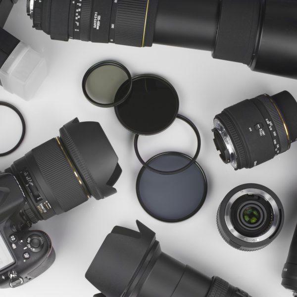 Eine Kamera und verschiedene Objektive auf hellem Untergrund.