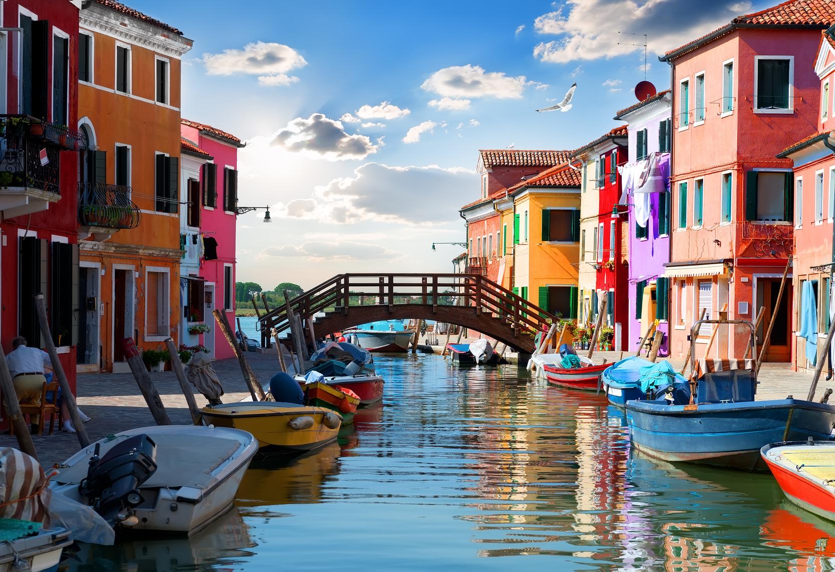Kanal mit Booten und farbenfrohen venezianischen Häusern.