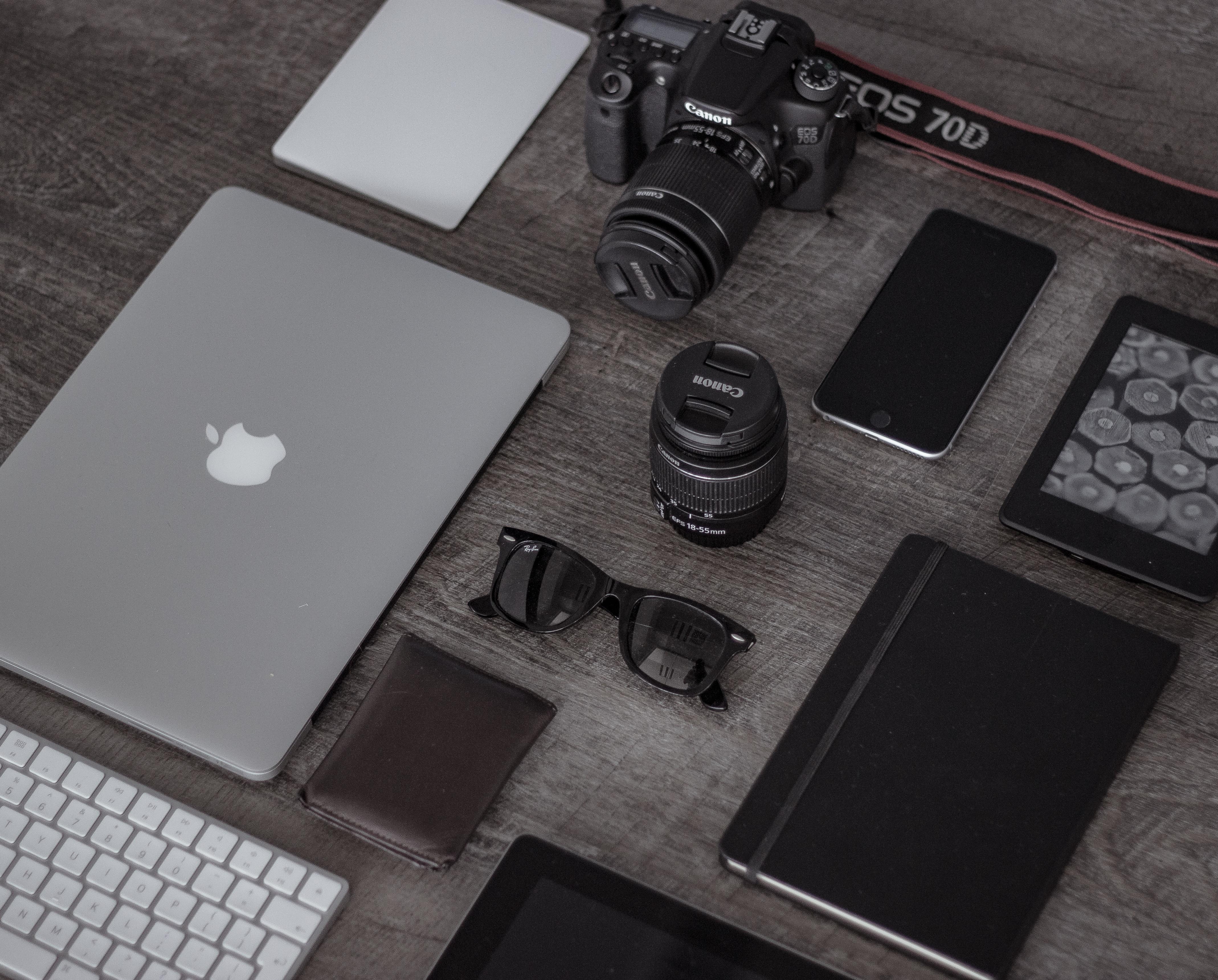 Notebook, Kamera, Smartphone auf einem Tisch liegend