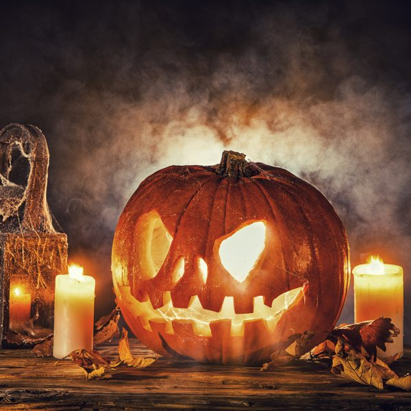 Ein geschnitzter Kürbis mit Gruselfratze mit Kerzen, spinnenwebenbedeckter Lampe vor nebeligem Hintergrund.