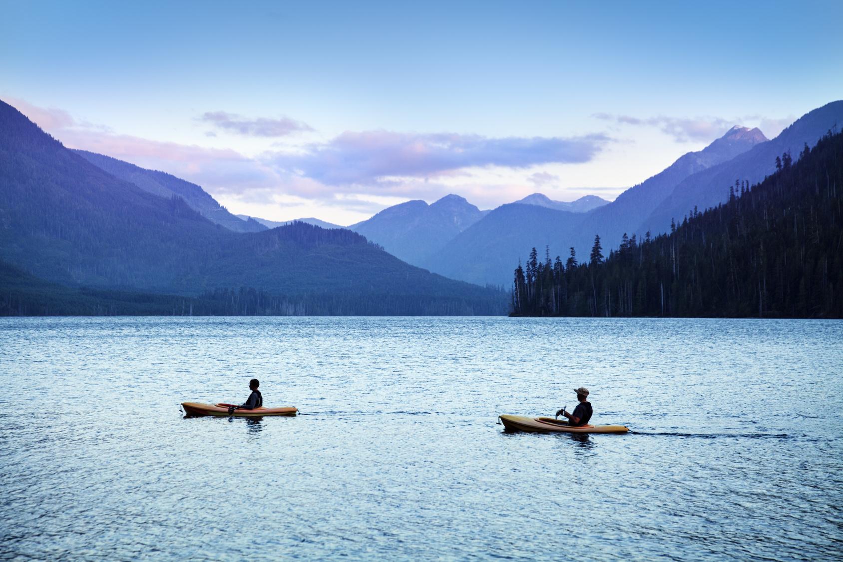 Zwei Kanufahrer auf einem See vor Bergkulisse.