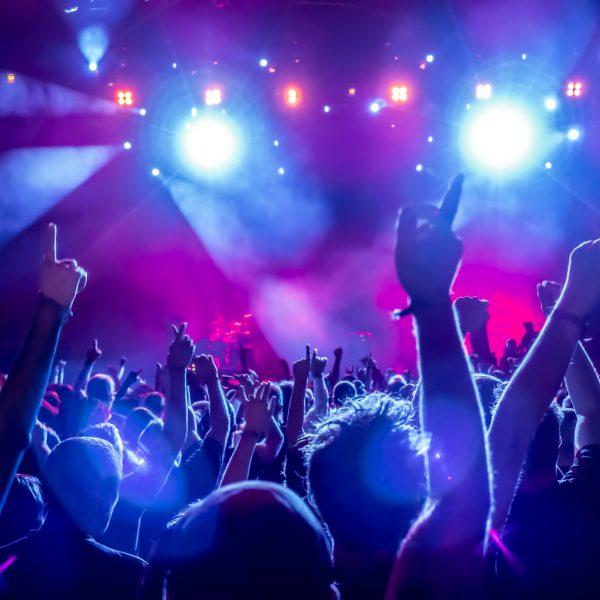 Konzertbesucher mit erhobenen Händen, zwei leuchtende Scheinwerfer im Hintergrund