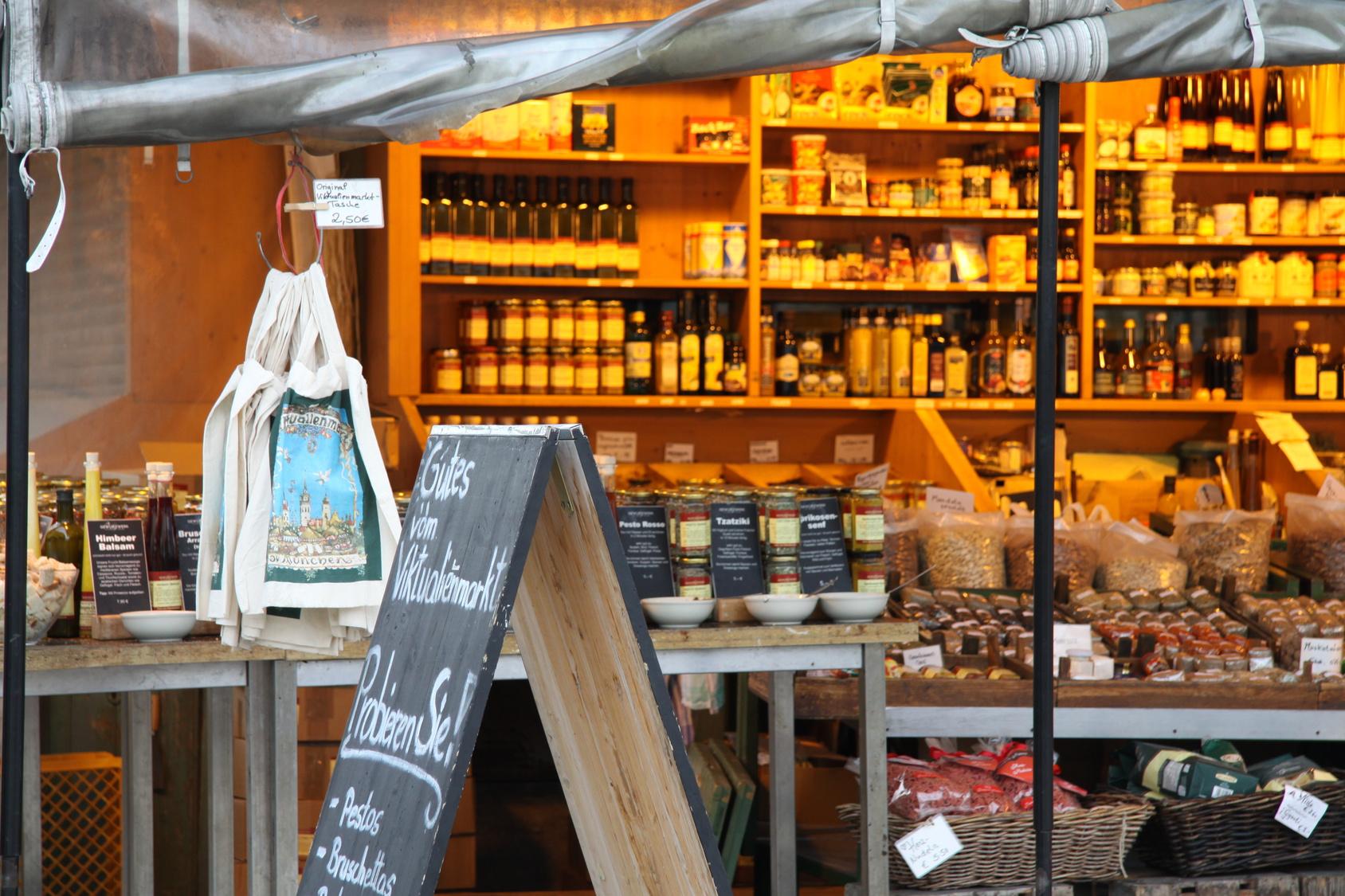 Fester Marktstand mit Regalen und Tischen voller Flaschen, Gläser und Verpackungen.