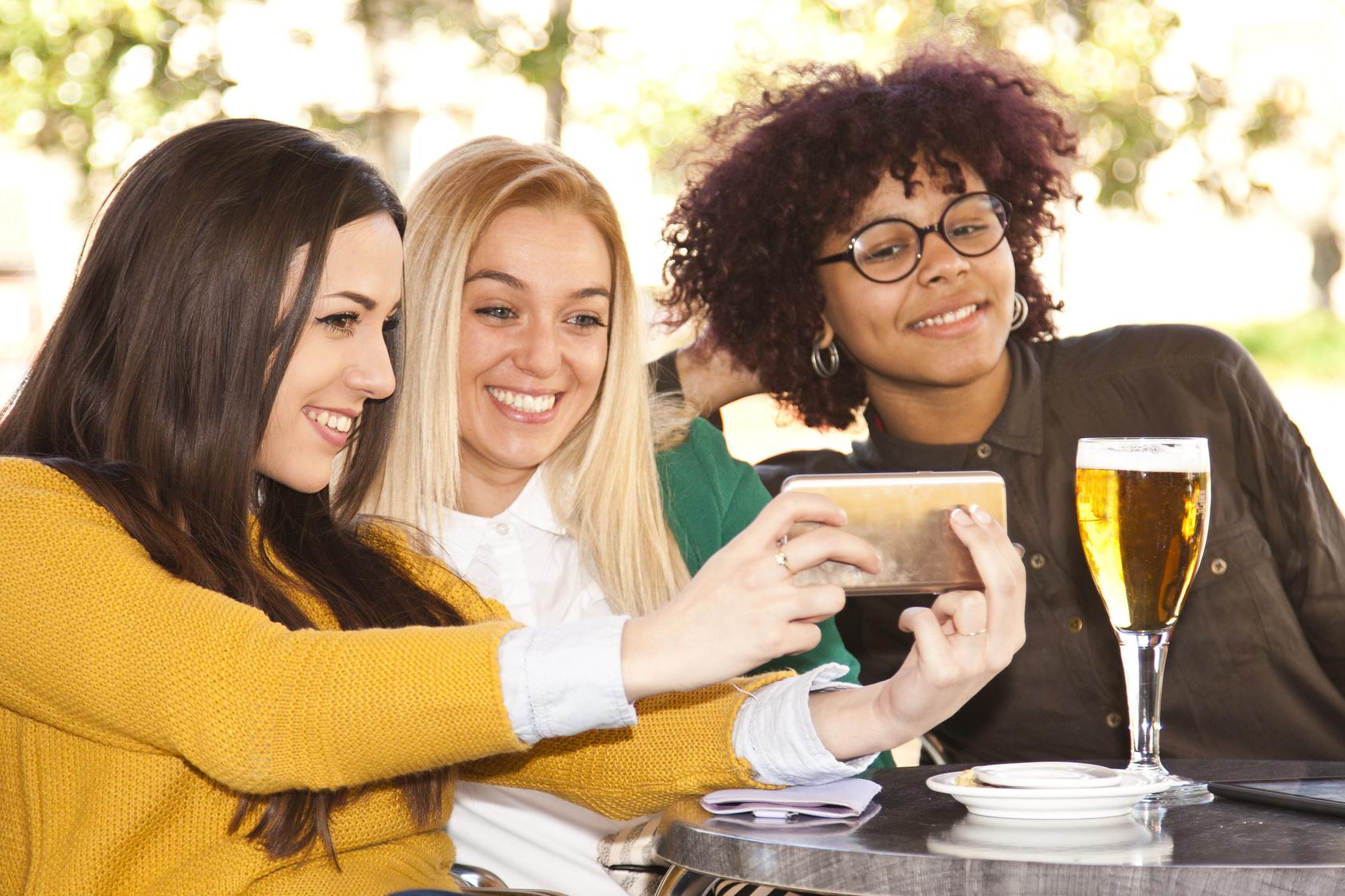 Drei junge Frauen machen ein Gruppen-Selfie