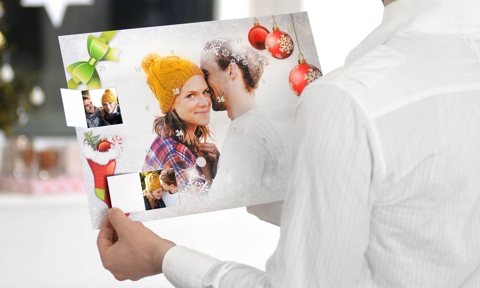 Jemand hält einen Foto-Adventskalender mit Bildern eines glücklichen Paares vor sich.