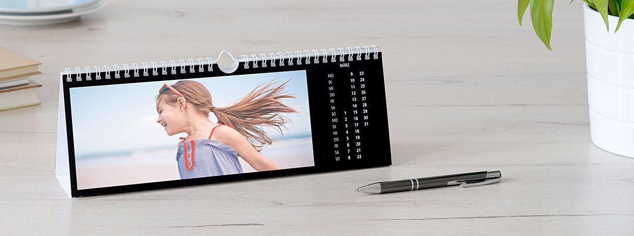 Tischkalender mit breitem Foto auf einem Bürotisch.