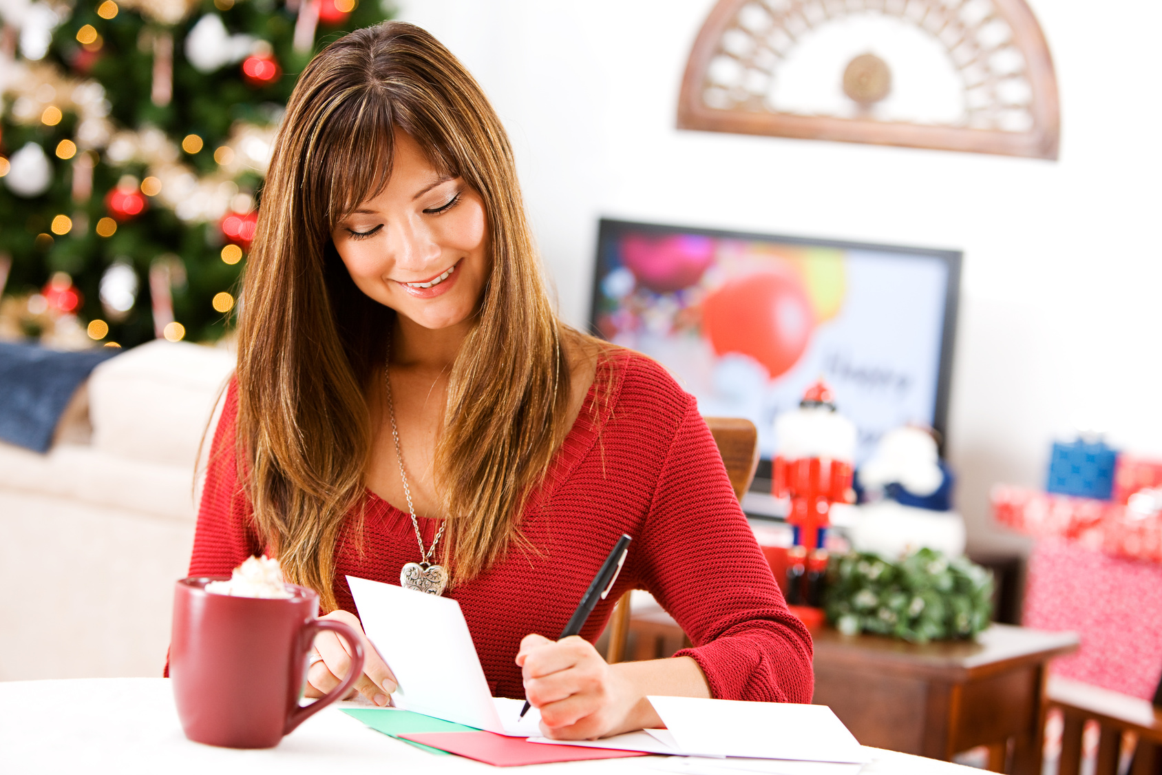 Frau sitzt am Tisch und schreibt Weihnachtskarten