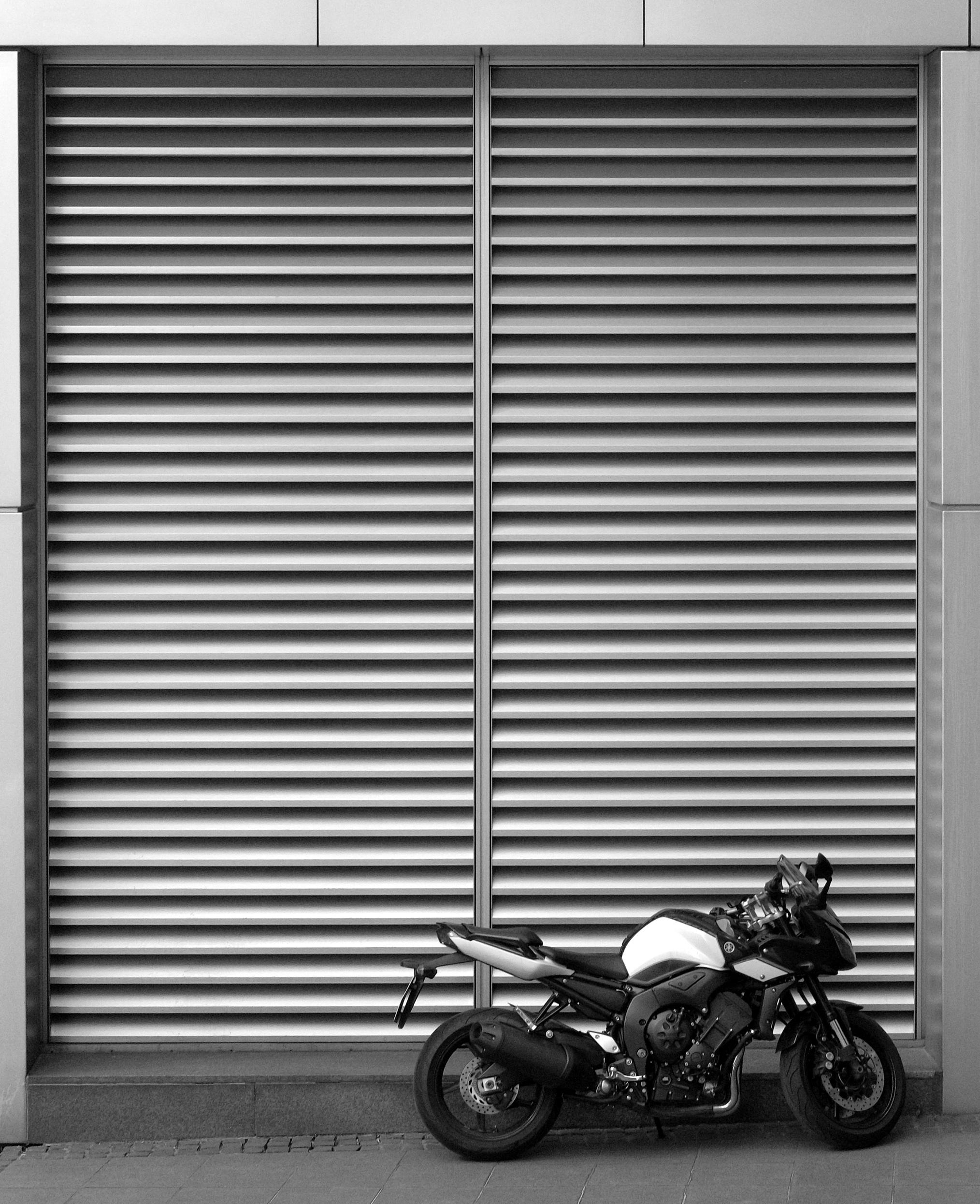 Motorrad vor Garagen-Rolltor aus Metall.