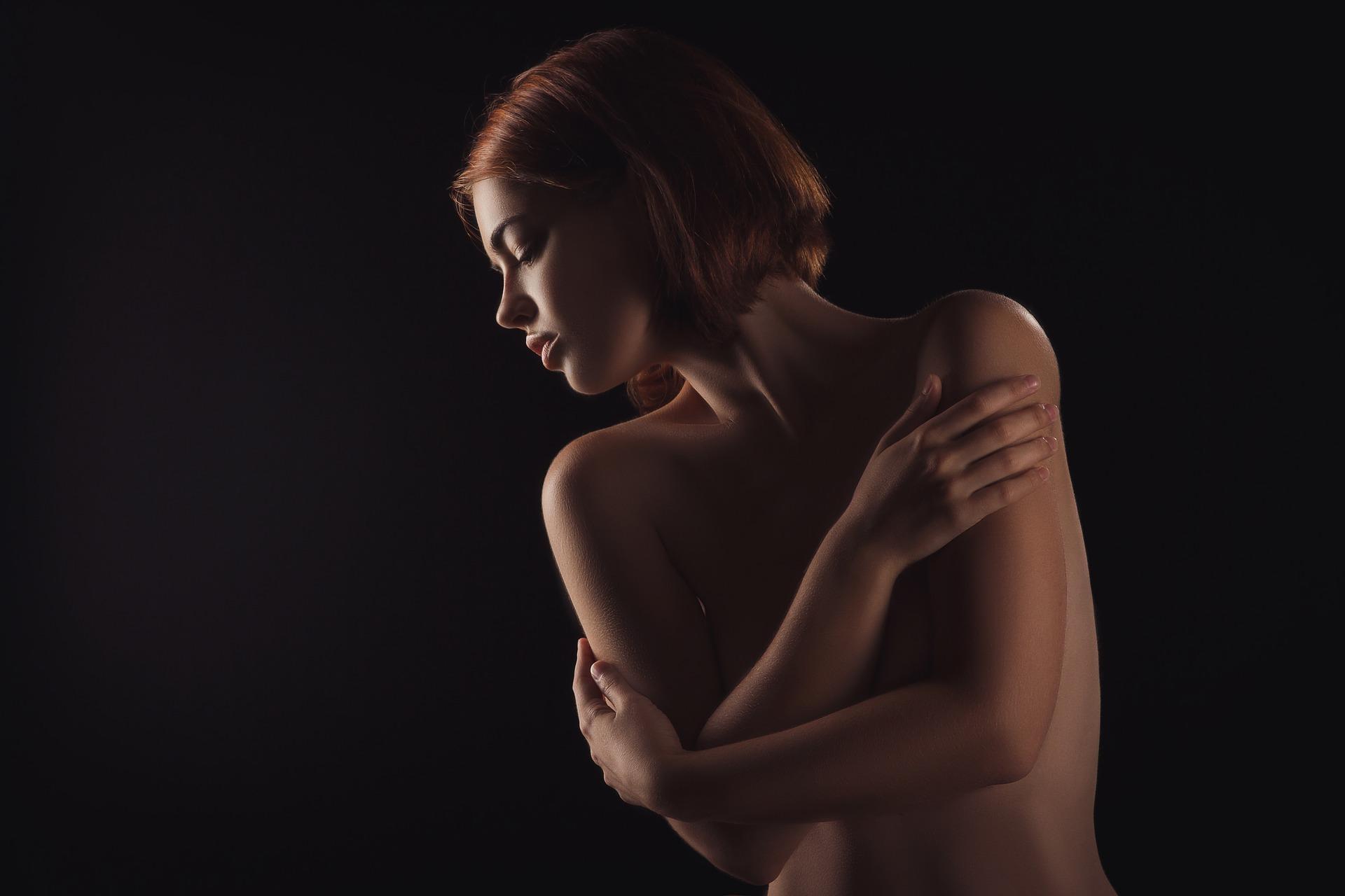 Frau mit nacktem Oberkörper, die ihre Arme vor ihren Brüsten verschränkt, vor schwarzem Hintergrund.