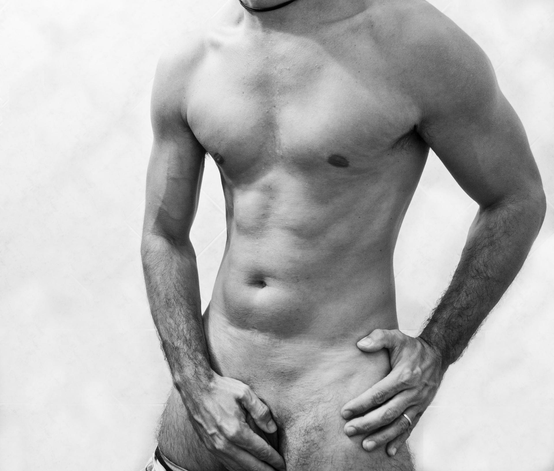 Ein muskulöser, nackter Mann, dessen Gesicht nicht zu sehen ist und der seinen Genitalbereich mit der Hand verdeckt.