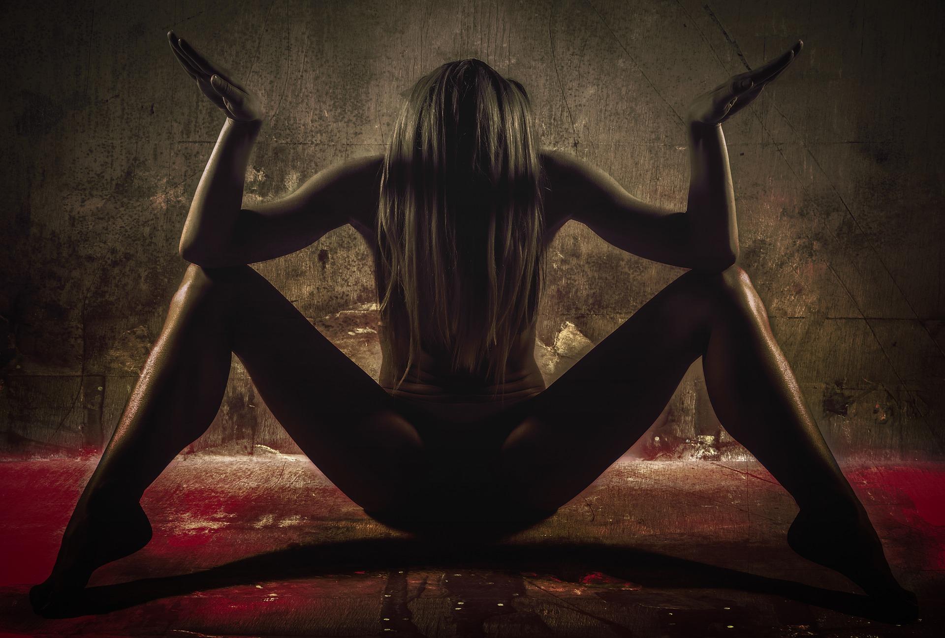 Aktfoto von Frau, die sitzend Arme und Beine spreizt – aufgrund des Schattens ist sie nur schemenhaft zu erahnen.