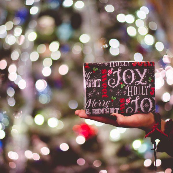 Geschenk in ausgestreckter Hand, im Hintergrund ein Weihnachtsbaum.