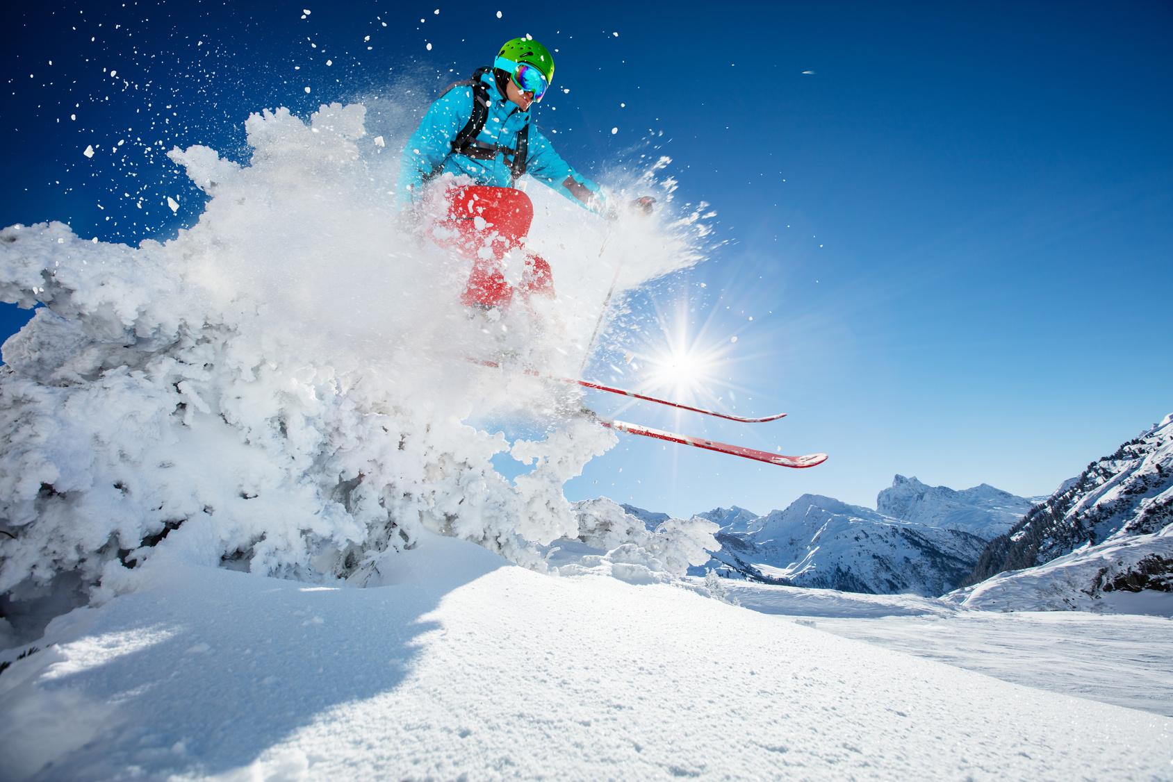 Ein Skifahrer hebt vor blauem Himmel ab und lässt Pulverschnee in alle Richtungen fliegen.