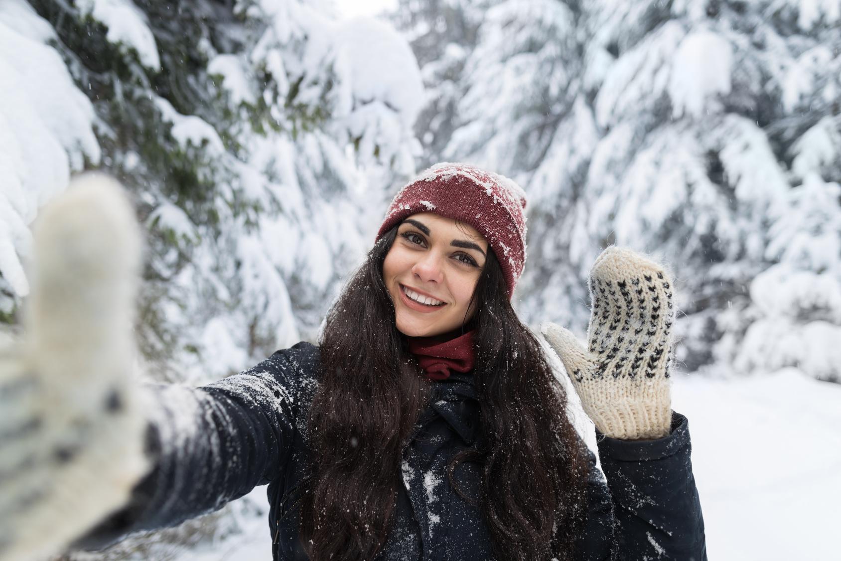 Eine junge Frau vor schneebedeckten Bäumen lacht in die Kamera.