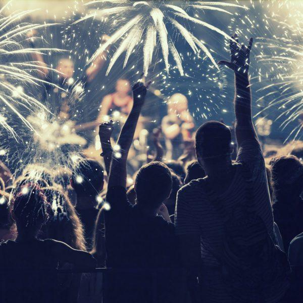 Feiernde Menschenmenge von hinten vor einem Feuerwerk