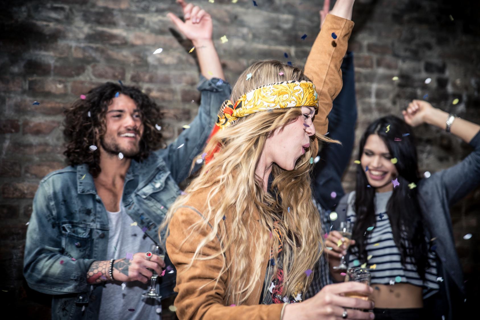 Feiernde junge Menschen im Konfettiregen.