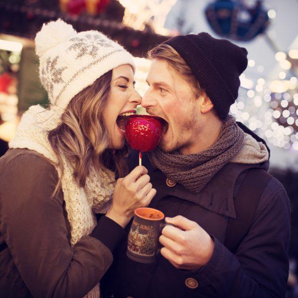 Ein junges Paar beißt auf dem Weihnachtsmarkt gemeinsam in einen kandierten Apfel.