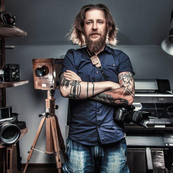 Fotograf mit Kamera in der Hand vor seinem Equipment.