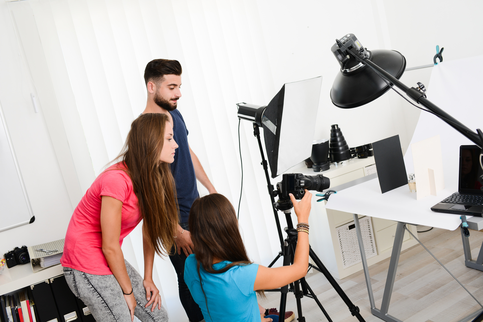 Drei Auszubildende machen Fotos von einer Flasche vor weißem Hintergrund.