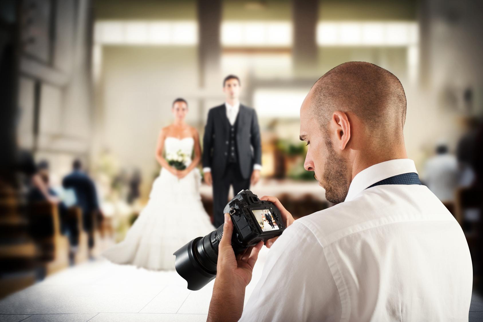 Fotograf prüft ein Bild vom Brautpaar auf seinem Kameradisplay.