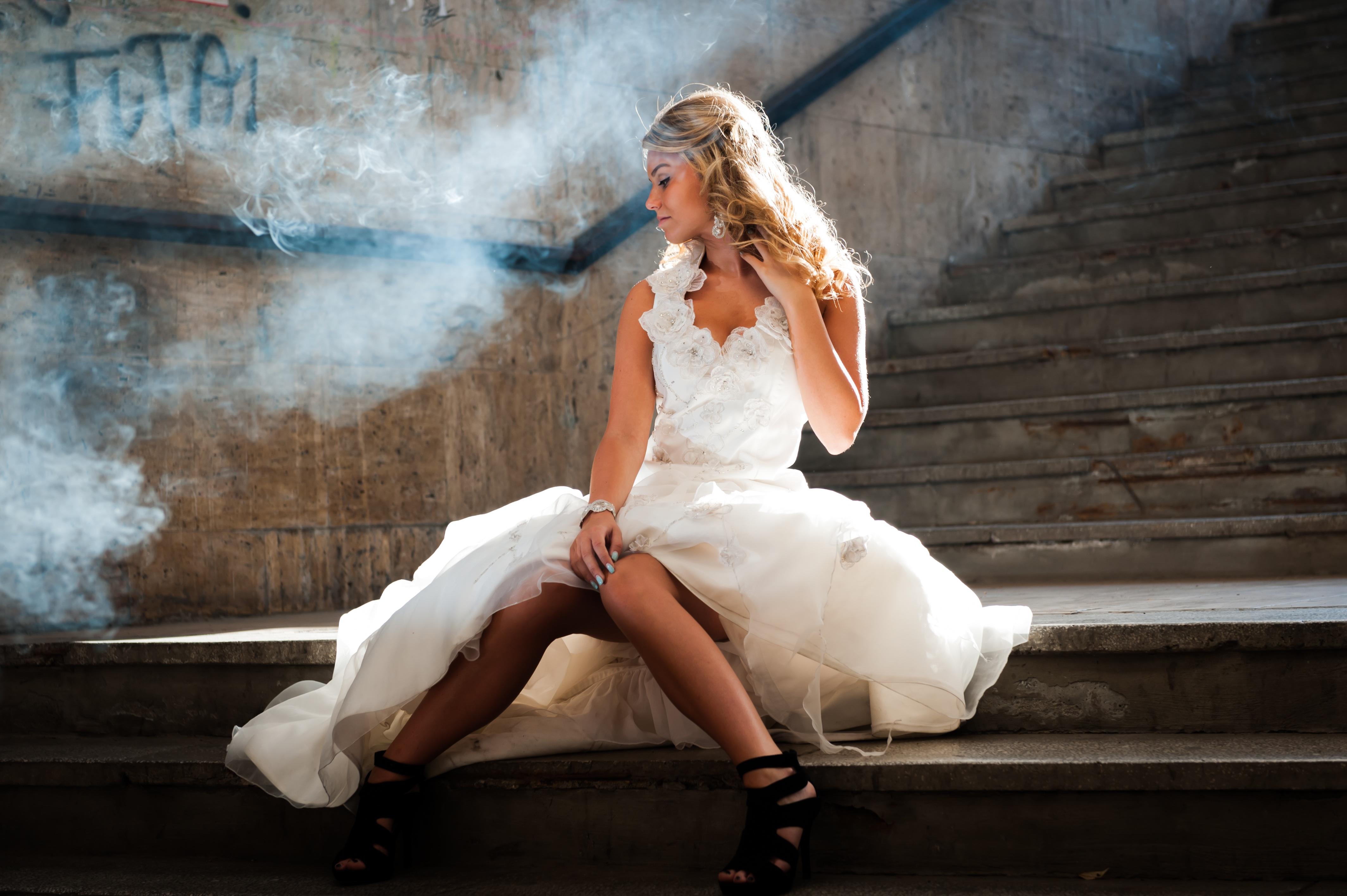 Frau in Hochzeitskleid sitzt auf einer Betontreppe – Nebelschwaden ziehen vorüber.