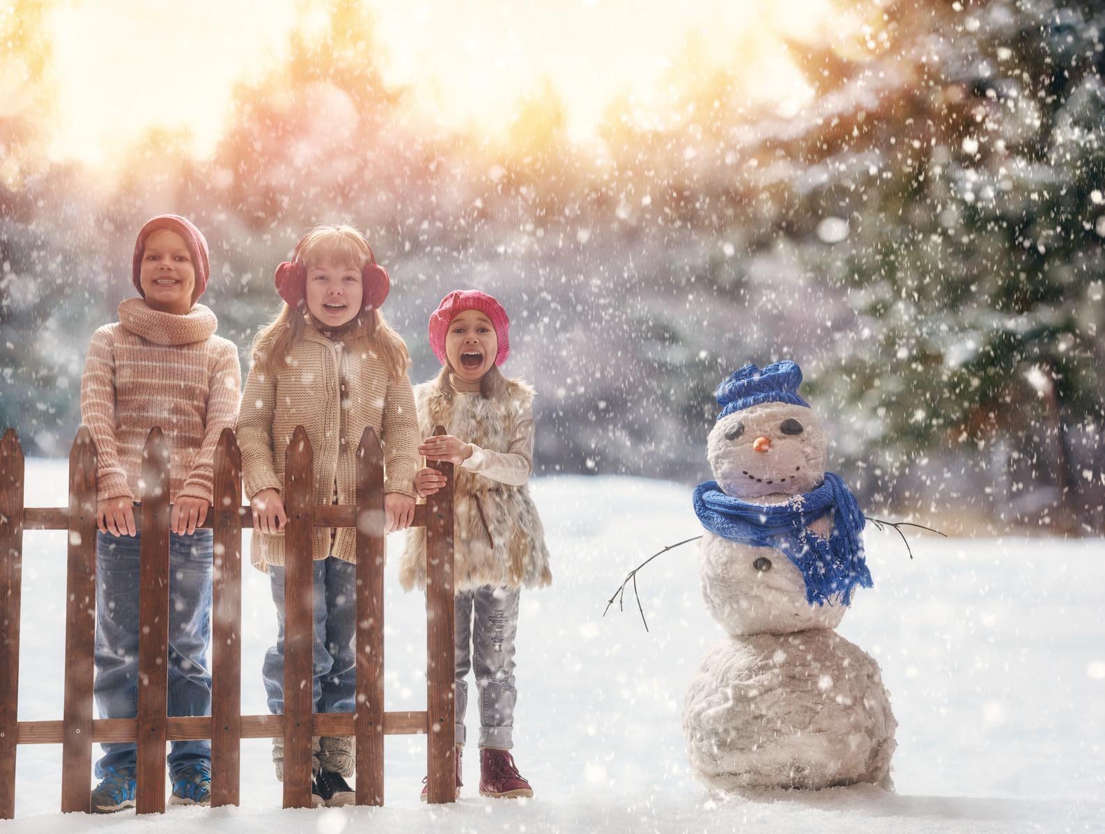 Drei Kinder mit Schlitten neben einem Schneemann.