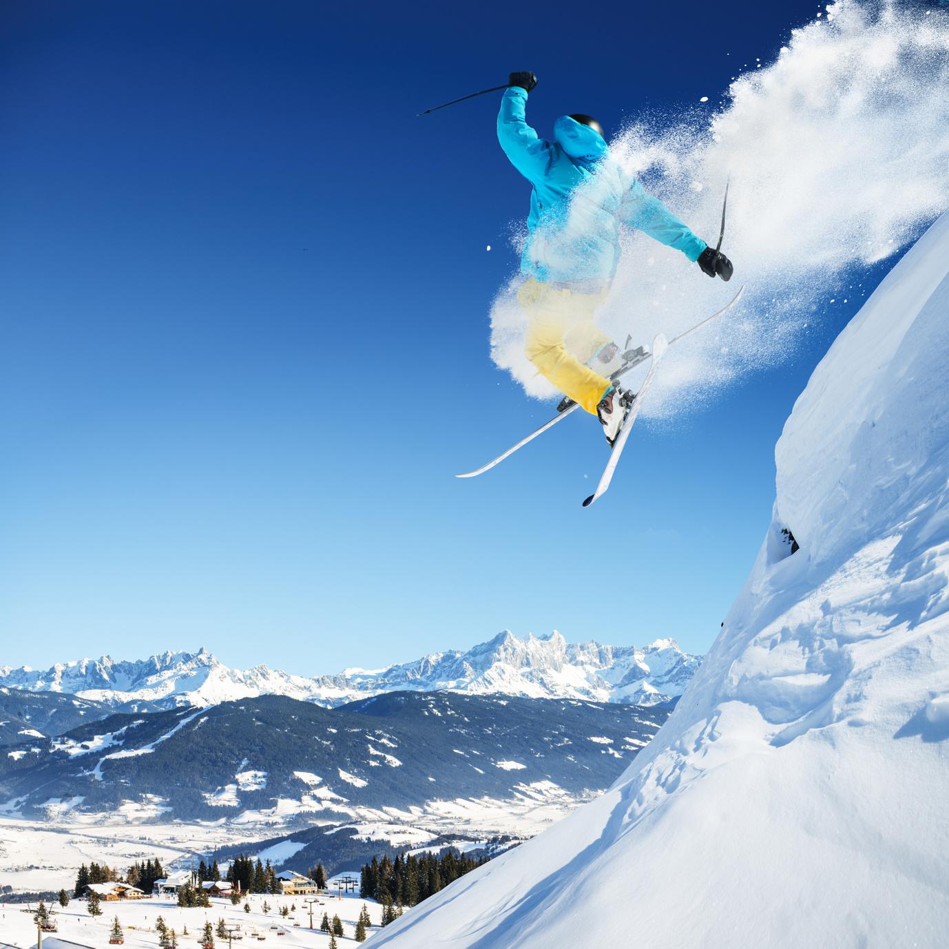 Springender Skifahrer im Tiefschnee vor blauem Himmel und verschneiter Berglandschaft.