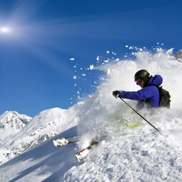 Ein Skifahrer braust in starker Rücklage durch den Tiefschnee und wirbelt dabei den Schnee auf.