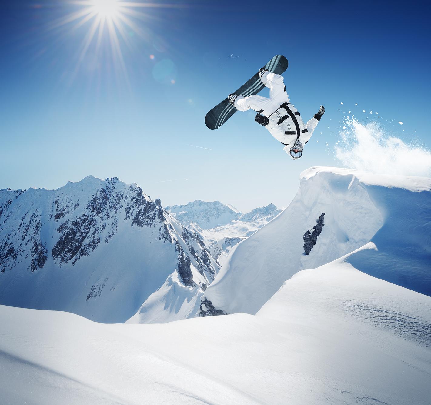 Ein Snowboarder beim Sprung, kopfüber in der Luft, vor traumhafter Bergkulisse.