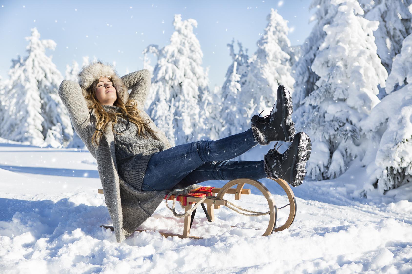 Eine Frau entspannt auf einem Schlitten und genießt den Sonnenschein vor schneebedeckten Tannen.