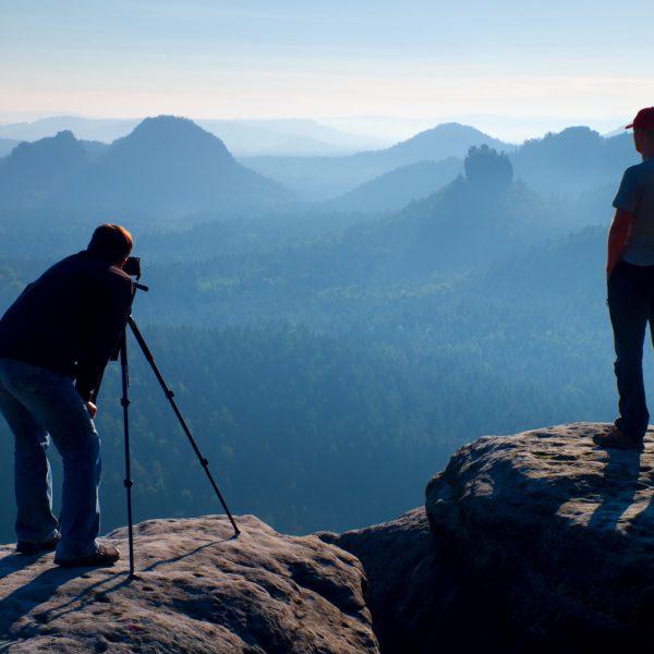 Zwei Fotografen mit Stativ vor Bergpanorama.