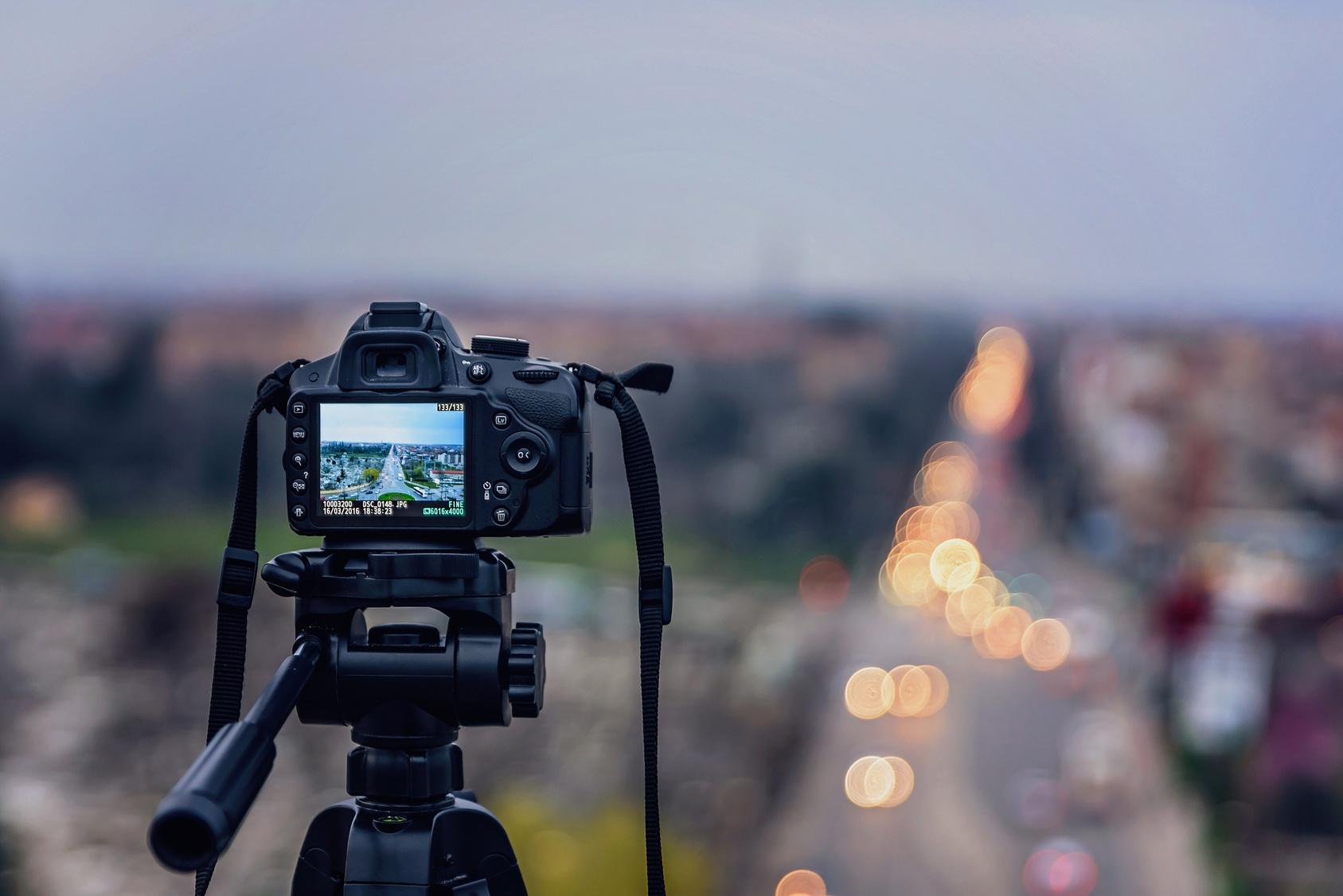 Kamera auf Stativ vor Stadtlandschaft.