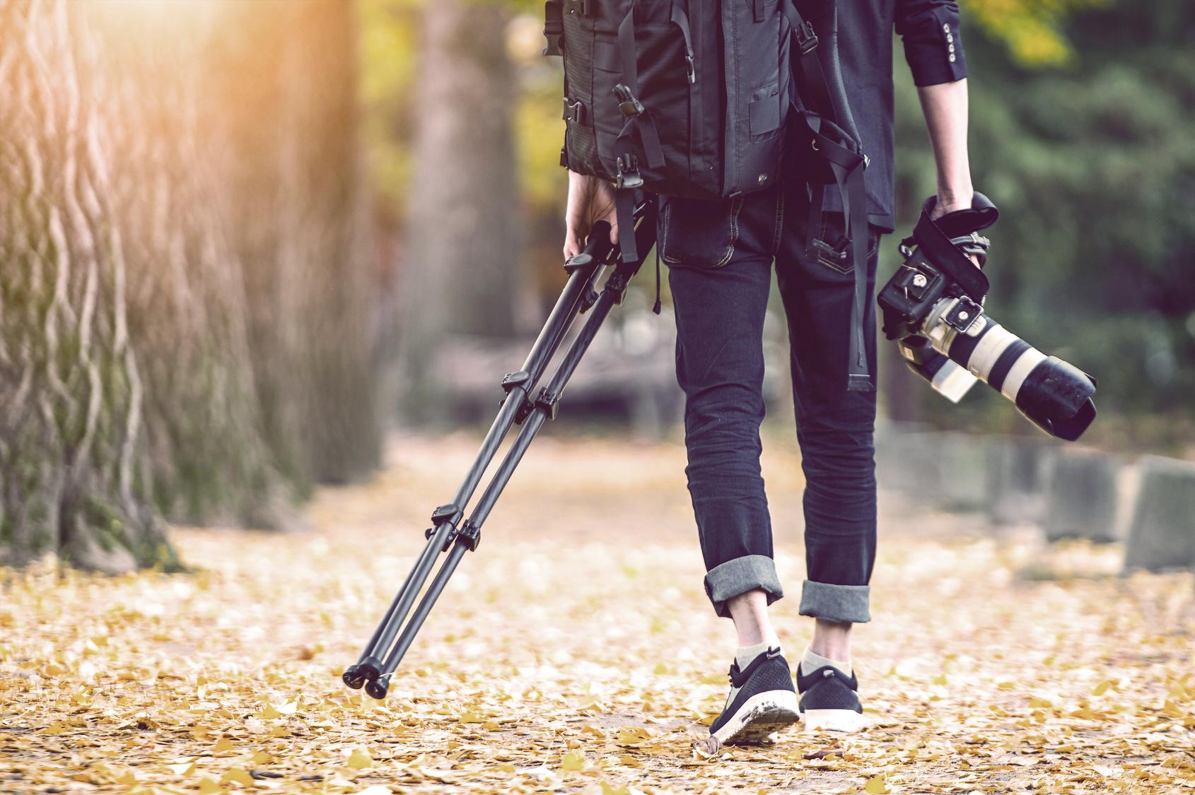 Fotograf mit Kamera und Stativ in den Händen spaziert durch herbstliches Laub.