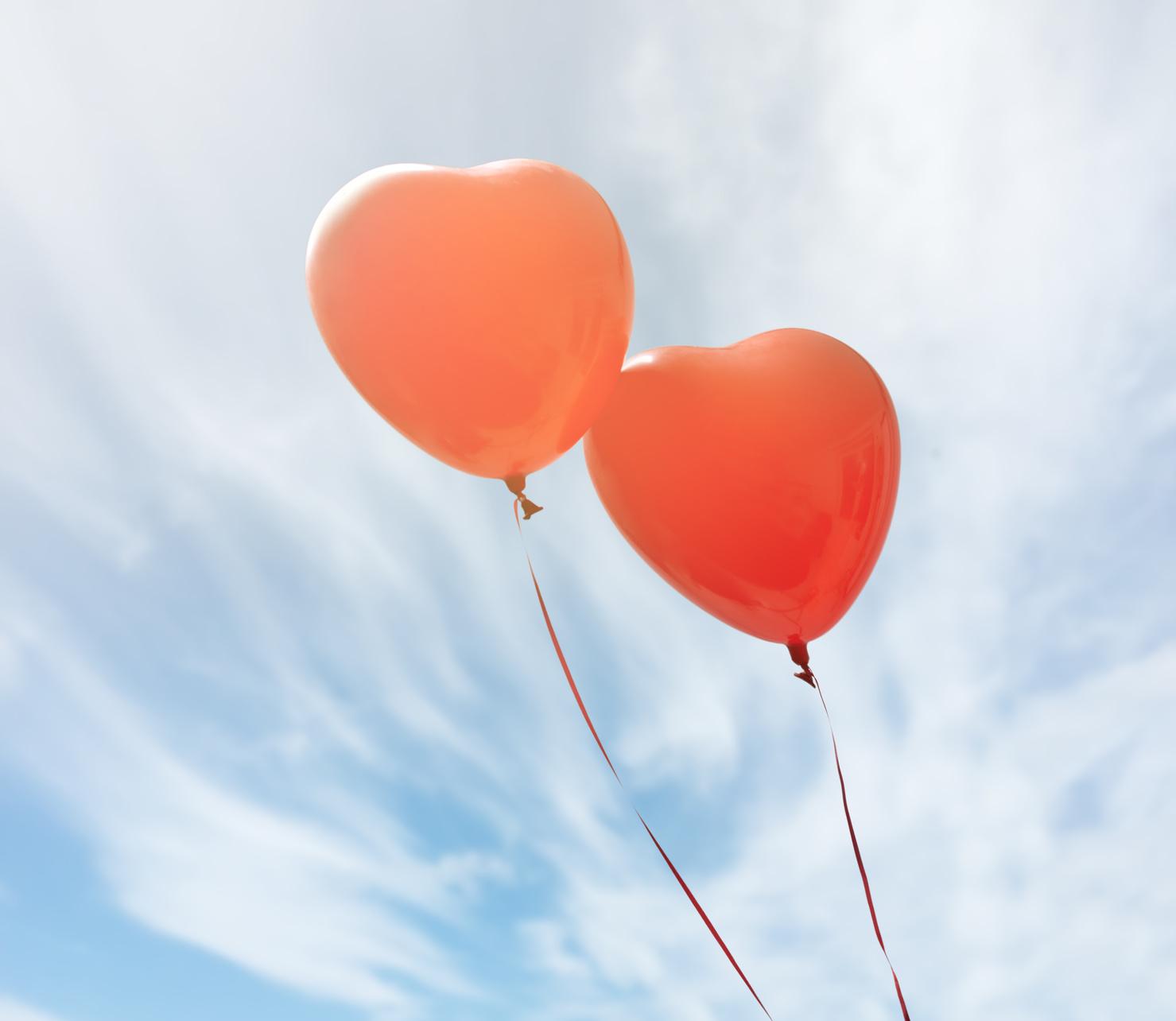 Zwei rote Luftballons in Herzform.