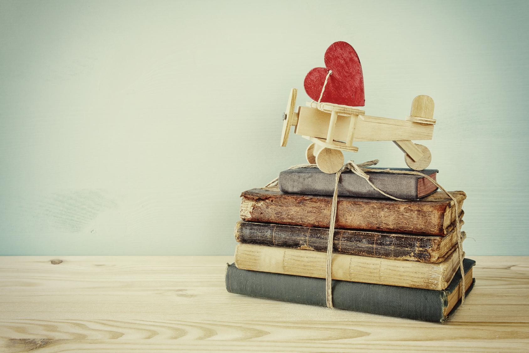 Ein Stapel antiker Notizbücher, obendrauf ein Holzflugzeug mit rotem Herz.