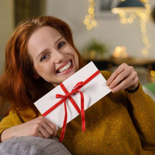 Lachende Frau hält Briefumschlag mit Geschenkschleife.