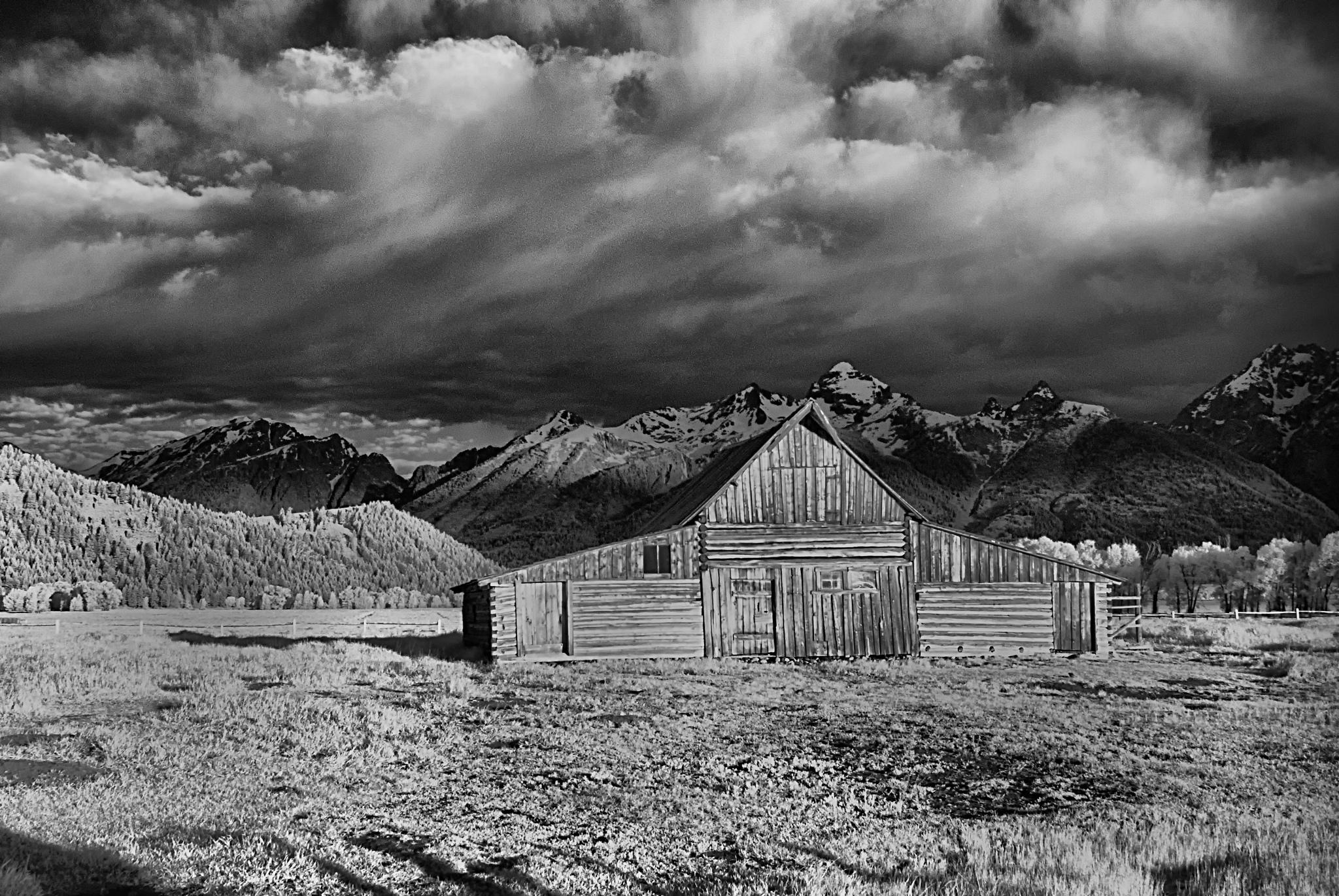 Rustikale Holzscheune vor Bergen und Wolken in Schwarz-Weiß.