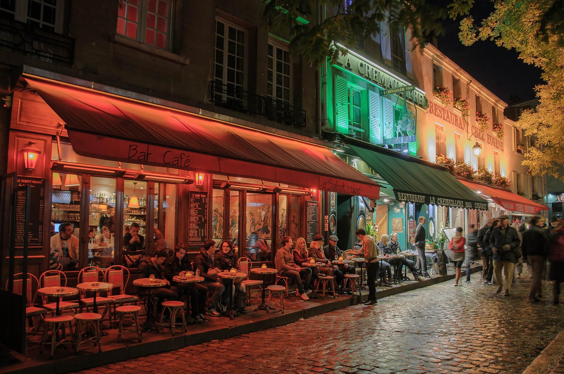 Menschen sitzen bei Nacht in Pariser Straßencafés.