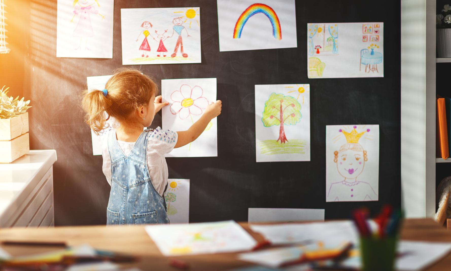 Kleines Mädchen hängt selbstgemalte Bilder an die Wand.