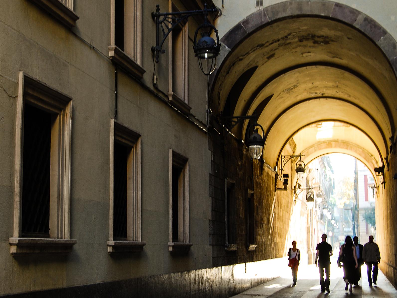 Menschen laufen durch überdachte Gasse im Barrio Gótico