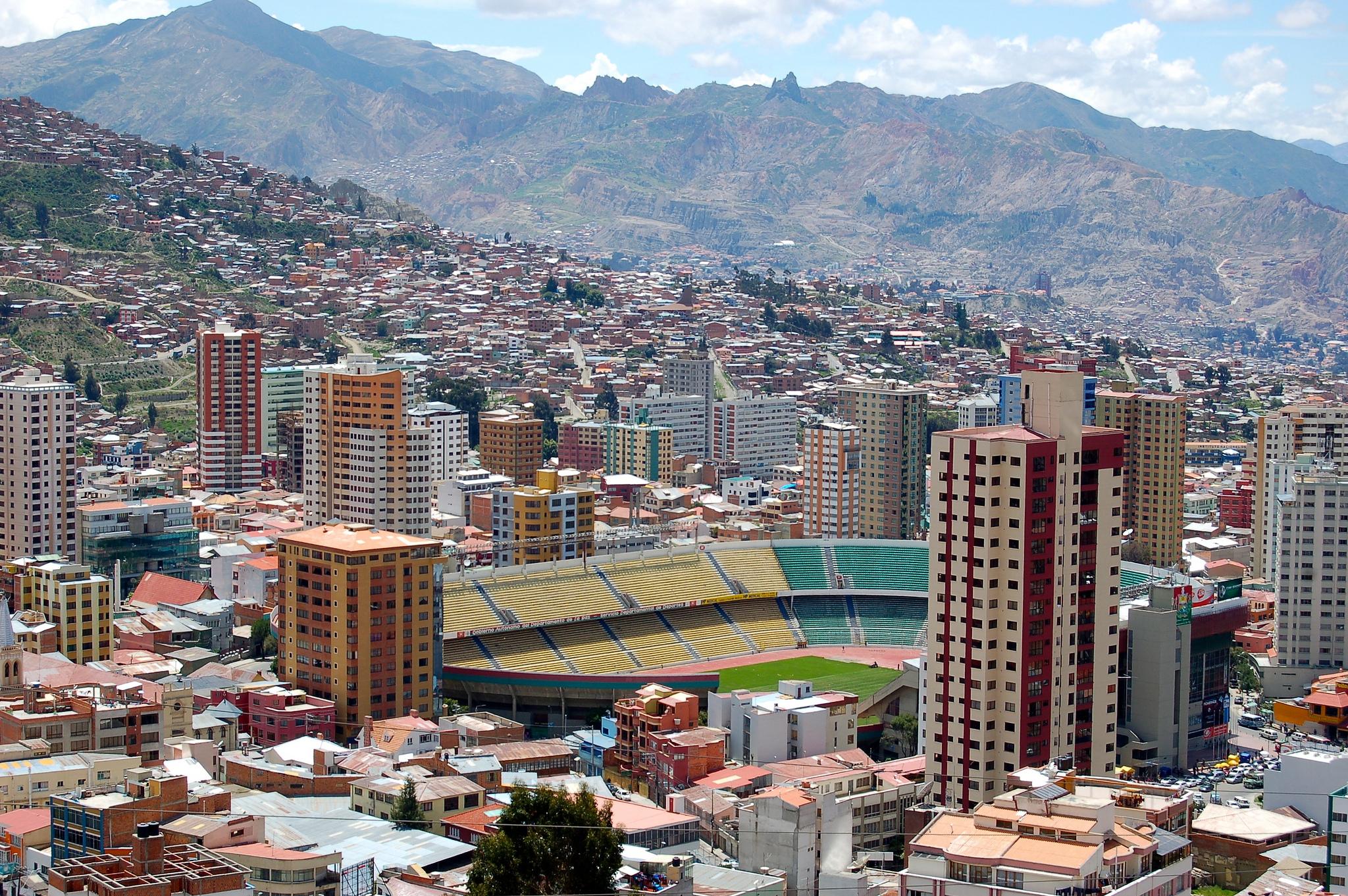Stadt-Panorama von La Paz mit Fußballstadion vor Gebirgskulisse, von Hochhäusern eingerahmt.