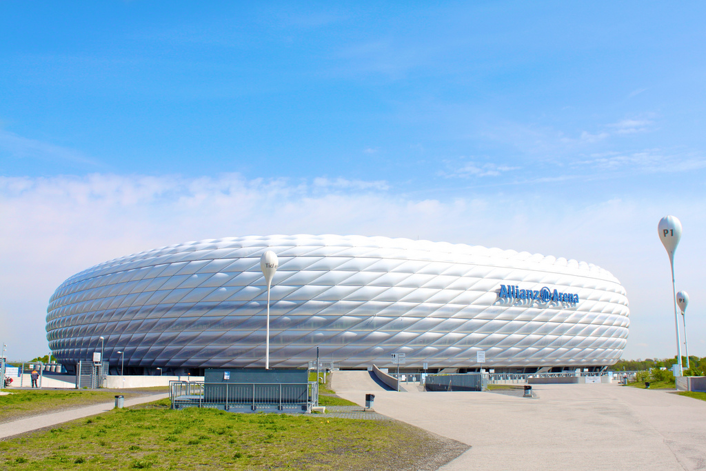Fußball-Stadion mit markanter, weißer Fassade in Rautenstruktur vor grünem Rasen und blauem Himmel.