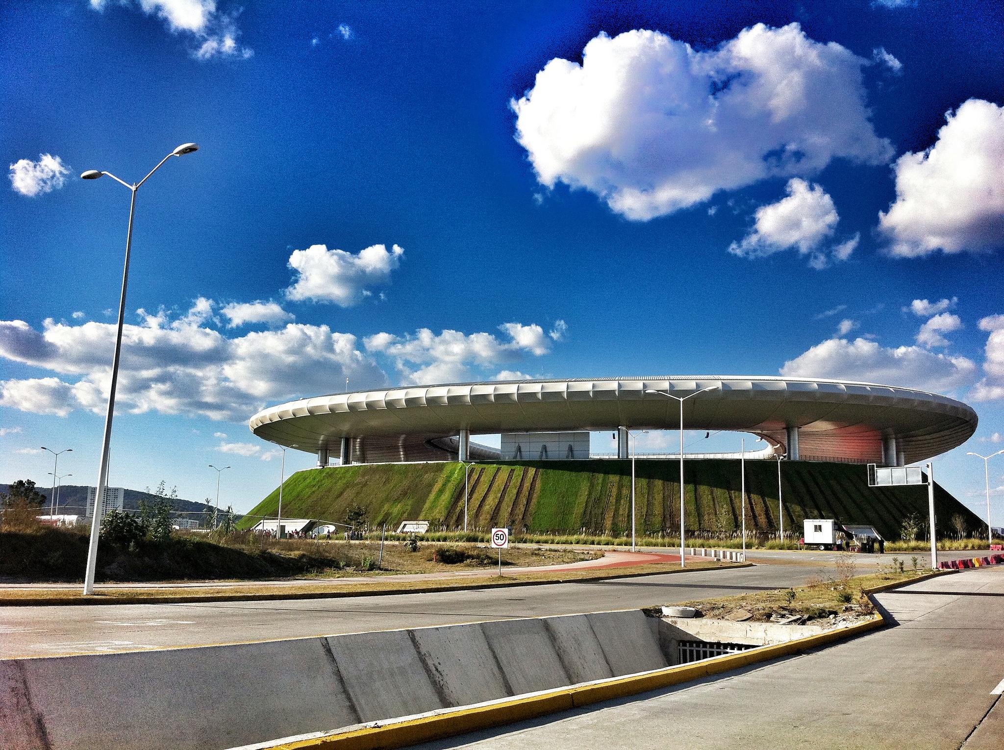 Ein kraterförmiges Stadion mit begrüntem Rand, unter weißem Runddach und blauem Himmel.