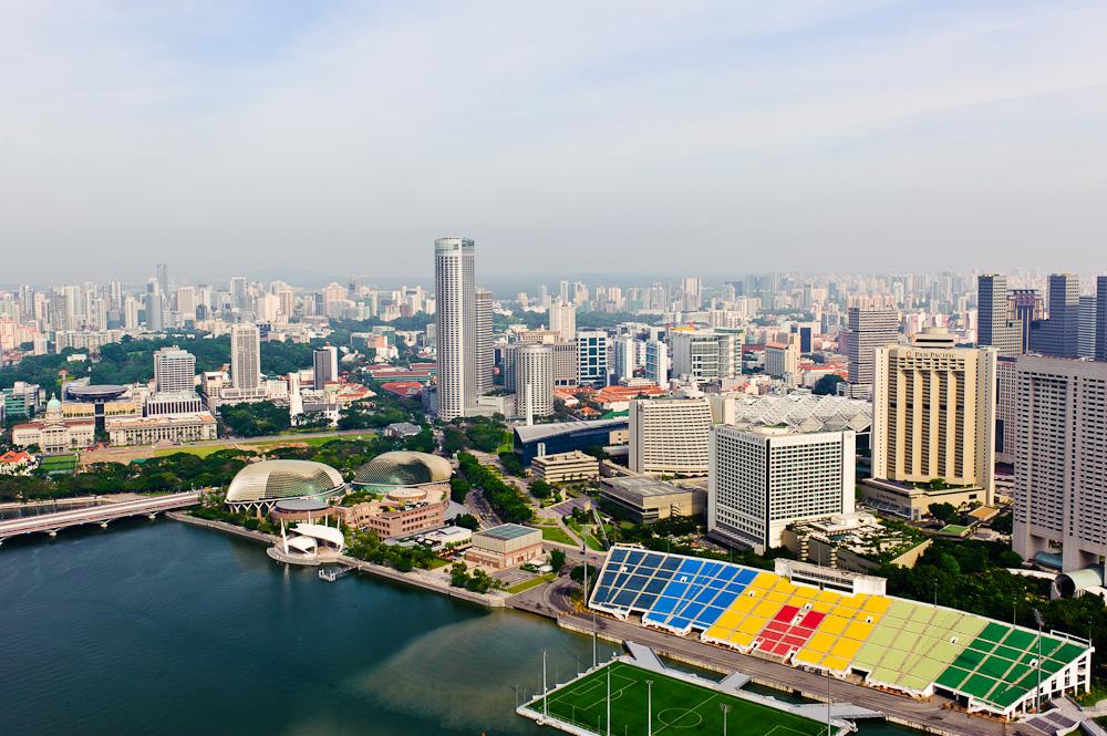 Stadt-Panorama von Singapur, Marina Bay. Im Vordergrund die Bucht und das schwimmende Fußballfeld vor der bunten Tribüne.
